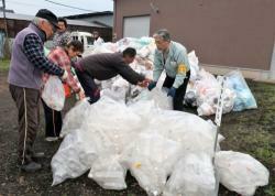 ペットボトル、プラスチック容器包装類にそれぞれ分けた袋を不燃ごみの集積場所に出す住民ら(舞鶴市今田)