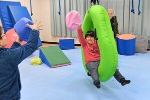 作業療法による診療で、遊具に乗りながらクッション投げを楽しむ山本君(昨年11月30日、京都市左京区・京都大)