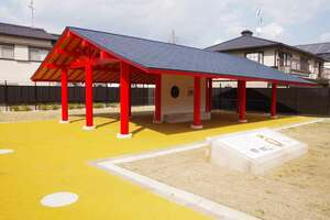 新設の案内板(手前)と復元された東屋。白色で示されているが柱穴跡=向日市鶏冠井町