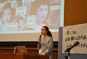 スクリーンに資料を写しながら日本語でスピーチする外国籍の青少年(精華町役場)