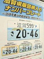 滋賀県の「図柄入りナンバープレート」をPRするポスター。カラー版に必要な寄付金が、県議をやきもきさせている