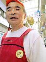 胸元に京都アニメーションを応援する缶バッジを着けた果物店の店員(京都市上京区・出町桝形商店街)