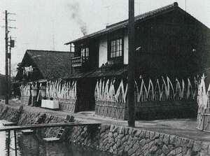 昭和40年頃の竹中精麦所。白川にかかる橋は、近くにあった製氷会社が氷の保存に使うおがくずを運ぶための道具名から「もっこ橋」と呼ばれたといい、今も残る(竹中さん提供)