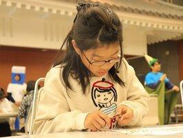 小刀を器用に使って鉛筆を削る出場者(南丹市園部町・市国際交流会館)