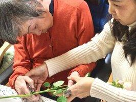 グループホームでいけばなに取り組む認知症のお年寄りをサポートする浜崎さん(京都市左京区・ケアサポートセンター宝ケ池)=浜崎さん提供