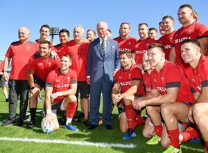 ラグビーW杯で4強入りしているウェールズ代表の練習会場を訪れ、選手たちと記念写真に納まる英国のチャールズ皇太子(中央)=23日午前、東京都内