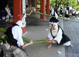 力強く刀を振り下ろし大蛇に見立てた竹を切る僧兵姿の地元住民たち(20日午後2時57分、京都市左京区・鞍馬寺)