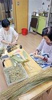 ちまき作りを習い一本一本丁寧に巻いてゆく月鉾保存会の女性たち(京都市下京区)