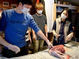 シカの足の肉を触る生徒たち。手分けしてさばいた(京都市左京区久多)