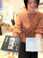 市販の納豆パックの形をした清水焼の納豆皿。ユニークな包装(左)で販売している=京都市上京区・堀川AC Lab