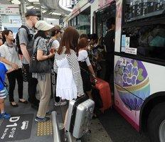 大きなキャリーバッグを持って、京都市バスに乗り込む観光客。車内混雑やダイヤの乱れの原因となっている(京都市下京区・京都駅バスターミナル)