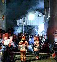 煙を上げる民家の前で消火活動にあたる消防隊員(28日午前5時半、京都市上京区)