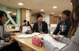 がん治療を受けながら大学生活を送る山口さん(中央)。授業後に同級生と談笑する=京都市左京区・京都大