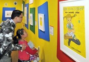 「長くつ下のピッピ」を描いた絵を熱心に見る来場者(8日、京都市下京区・美術館「えき」KYOTO)