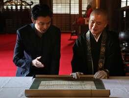 光秀が西教寺に出したとされる「供養米寄進状」の説明を受ける長谷川さん(左)=大津市坂本5丁目・西教寺