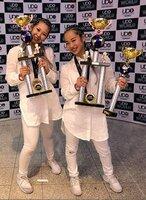 優勝のトロフィーを手にする広嶋さん(左)と櫻谷さん=8月、UDO JAPAN提供