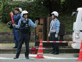 電気自動車から交差点脇のボックスに電線をつないで信号を作動させる警察官たち(福知山市内記・福知山市役所前)