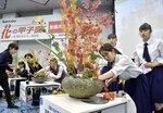 花ばさみをバトン代わりに、3人で協力して作品を仕上げていく高校生(京都市中京区・池坊会館)