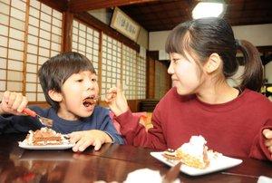 チョコレートケーキを宗汰君(左)に分ける中林さん=向日市上植野町