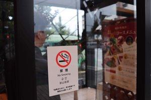 焼肉店が「禁煙」方針を伝えるため、出入り口に掲示したステッカー(京都市西京区)