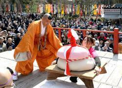 力を込めて巨大な鏡餅を持ち上げる女性参加者(京都市伏見区・醍醐寺)