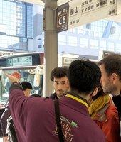 嵐山へ向かう京都バス「73」乗り場で、案内スタッフに英語で確認する観光客