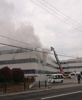 出火し、煙を上げるファルコバイオシステムズ総合研究所(京都府久御山町)