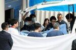 ストレッチャーで病院内に運ばれる青葉真司容疑者(14日午前10時17分、京都市内の病院)=画像の一部を加工しています