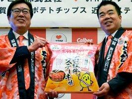 「近江牛ステーキ味」のポテトチップスを贈る伊藤社長(左)=大津市・県公館